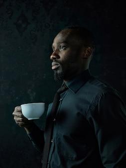어두운 스튜디오에서 포즈를 취하는 커피의 흰색 컵과 세련 된 젊은 아프리카 흑인 남자.