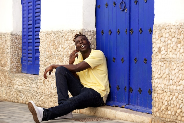 Stylish young african man sitting outside and talking on mobile phone