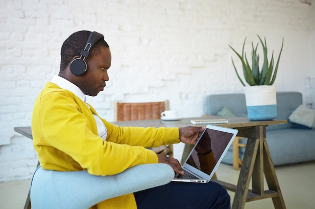 Stylish young afro american man sitting in chair at home, multitasking, using laptop and headphones, having serious facial expression. people, technology, communication and modern lifestyle