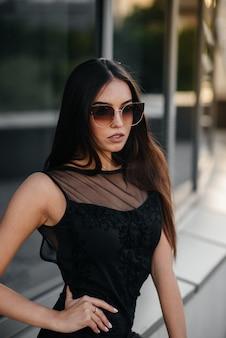 세련 된 젊고 섹시 한 여자 블랙에서 비즈니스 센터 앞에서 포즈. 패션과 스타일