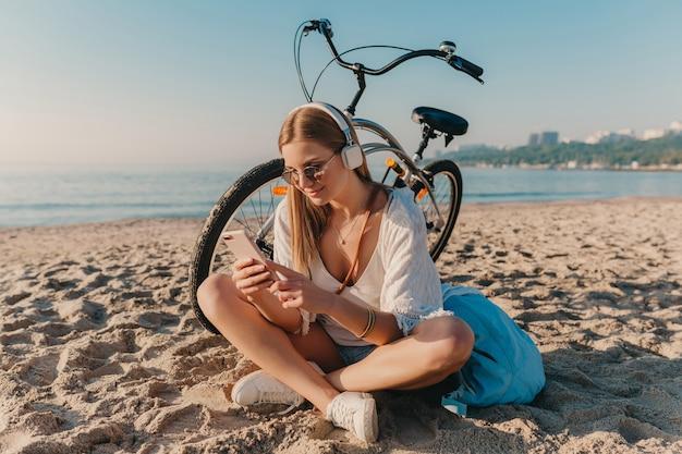 Elegante giovane donna sorridente bionda attraente che si siede sulla spiaggia con la bicicletta in cuffie che ascolta la musica