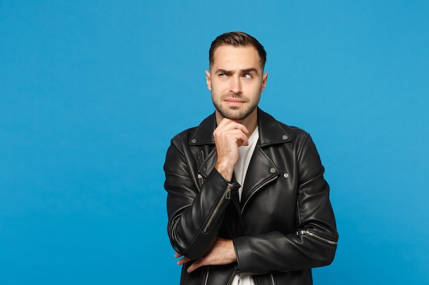 Stylish young bearded man in black leather jacket white t-shirt put hand prop up on chin isolated on blue wall background studio portrait. people sincere emotions lifestyle concept. mock up copy space