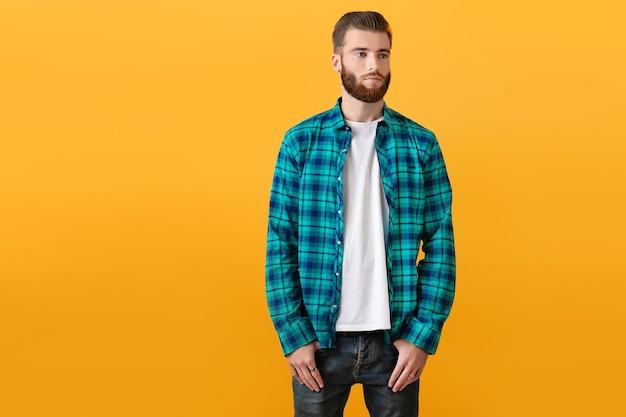 ファッション トレンド スタイルのアパレルが黄色の背景にポーズをとって格子縞のシャツを着たスタイリッシュな若いひげを生やした男