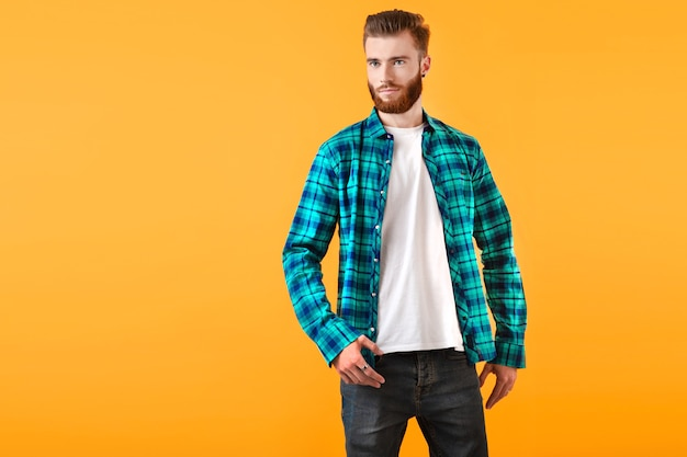 黄色の壁のファッショントレンドスタイルのアパレルでポーズをとってチェックシャツのスタイリッシュな若いひげを生やした男
