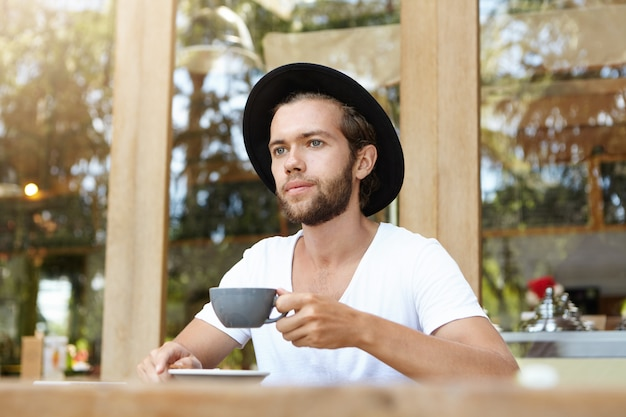 Elegante giovane uomo barbuto che indossa t-shirt bianca e cappello nero che tiene tazza di caffè o tè, gustando una bevanda calda prima di pranzo al ristorante sul marciapiede