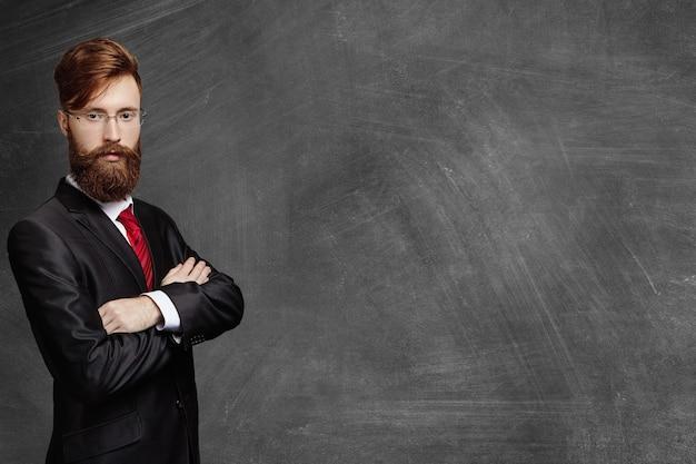 Elegante giovane professore barbuto in bicchieri in piedi alla lavagna vuota, tenendo le braccia incrociate e guardando con espressione seria o arrabbiata.