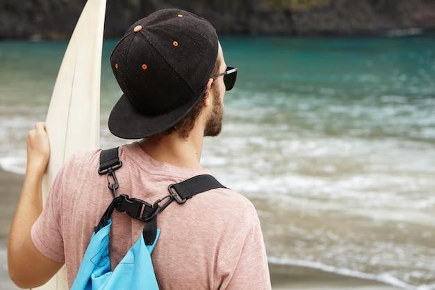 Elegante giovane surfista barbuto che indossa occhiali da sole e snapback guardando le onde del mare blu, mentre in piedi sulla spiaggia di sabbia con il suo bodyboard. sport, estremo, hobby