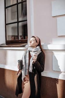 Стильная молодая красивая девушка с рыжими волосами гуляет по городу в осенней одежде с пальто и шарфом. наряд на холодную погоду