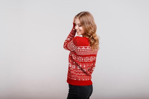 灰色の背景にトレンディなヴィンテージの赤いセーターのスタイリッシュな若い美しい幸せな女の子