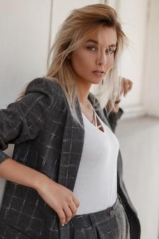 거리에서 세련된 빈티지 회색 정장을 입고 날카로운 시선을 가진 세련된 젊은 아름다운 모델 여자. 카메라에 보이는 모델 소녀