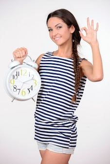 Stylish young beautiful woman hold a big alarm clock.