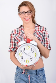 Stylish young beautiful woman holding a big alarm clock
