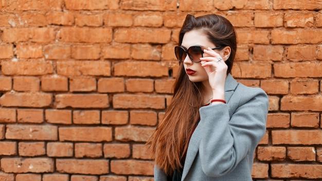 レンガの壁の近くの灰色のコートにサングラスをかけたスタイリッシュな若い美しい女性