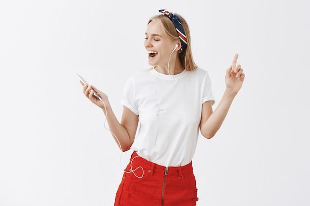 Elegante giovane ragazza bionda in posa contro il muro bianco