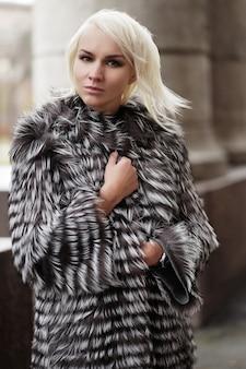 冬の外観を身に着けているスタイリッシュな若いブロンドの女性