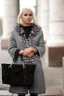 겨울 모습을 입고 세련 된 젊은 금발 여자