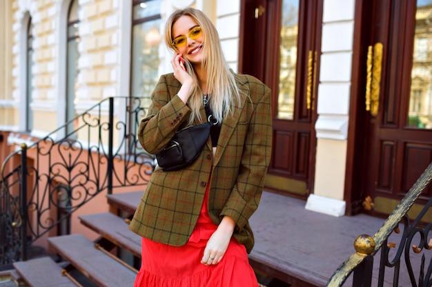 スタイリッシュな若いブロンドの女性が高級店の近くでポーズし、彼女のスマートフォン、ファッショナブルなモダンな服、特大のジャケット、お尻のバッグで話します。