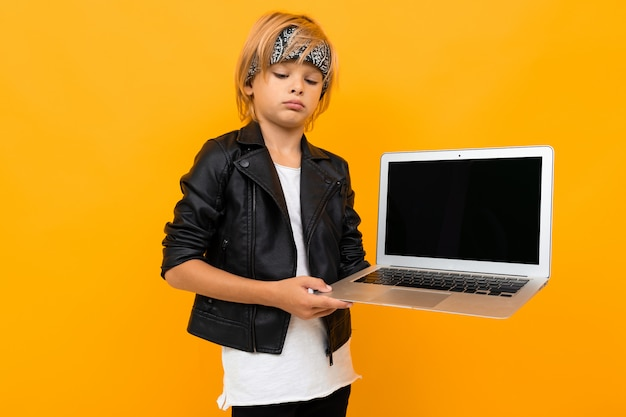 Stylish young boy in black jacket and white t-shirt shows his laptop