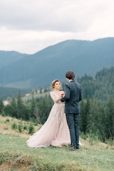 Stylish young bride and groom stand in boat on background cloude sky sea and mountains of montenegro