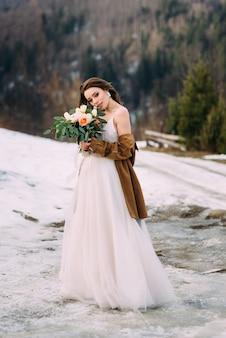 花の花束を持つスタイリッシュな若い花嫁は、美しい一日を楽しんでいます。