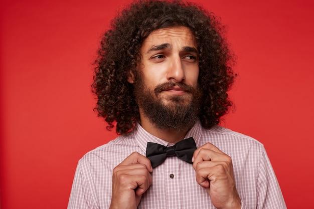 Стильный молодой брюнет кудрявый бородатый мужчина морщит лоб и держит черный галстук-бабочку, глядя в сторону, нахмурив брови, стоя на красном фоне