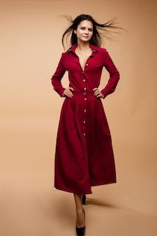 赤いドレスのスタイリッシュな若いブルネットの女性モデル