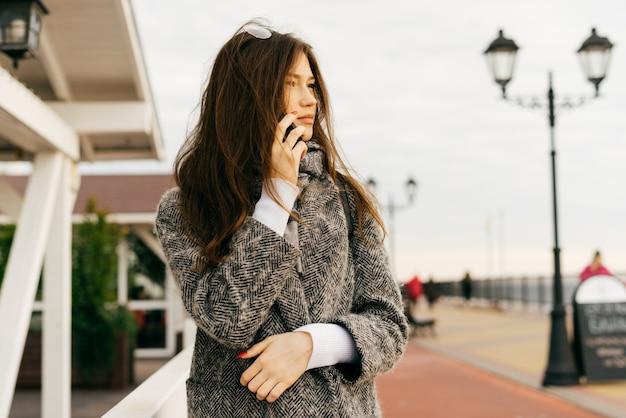Стильная молодая брюнетка девушка в сером пальто разговаривает по телефону, на открытом воздухе, в пасмурный день, уличная мода