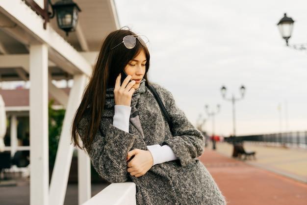 Стильная молодая брюнетка девушка в сером пальто разговаривает по телефону на открытом воздухе