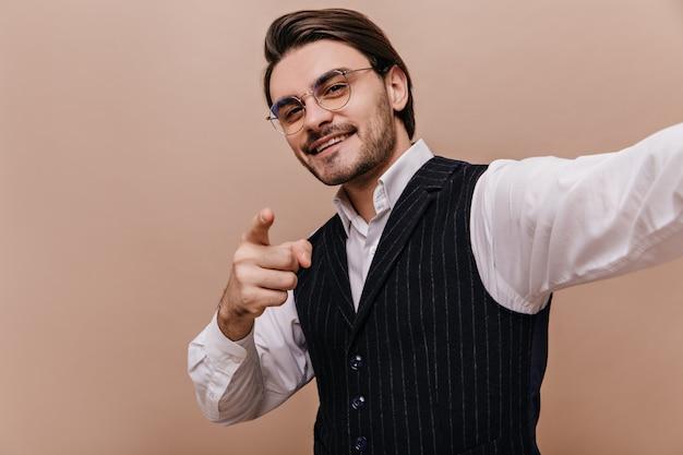 Elegante giovane bruna con gli occhiali, camicia bianca e gilet a righe nere, sorridente, indicando e guardando nella fotocamera e facendo selfie contro il semplice muro beige