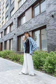 도시 거리의 배경에 세련된 새 여름 옷 컬렉션에서 포즈를 취하는 커피와 함께 세련된 젊은 갈색 머리 모델