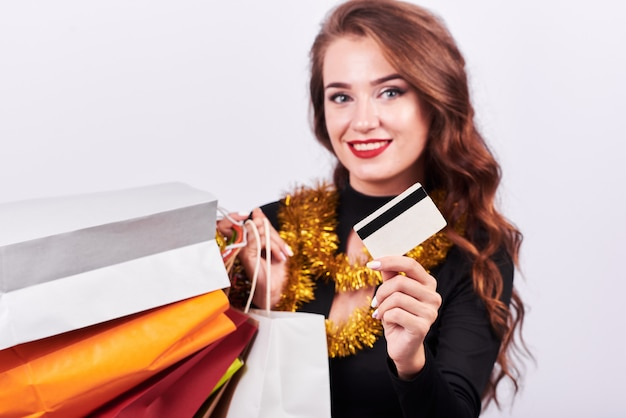 Stylish young brunette woman holding colorful shopping bags and credit card