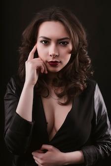 スタジオで革のジャケットのスタイリッシュな若いブルネットの女性