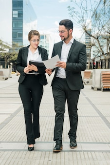 Stylish young businessman and businesswoman looking at document while walking on the pavement