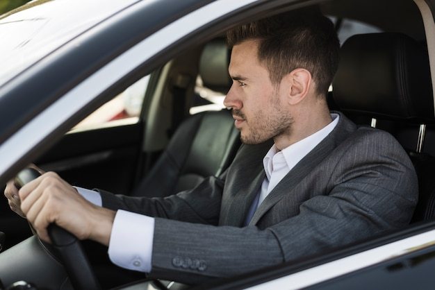 スタイリッシュな若い実業家の車を運転