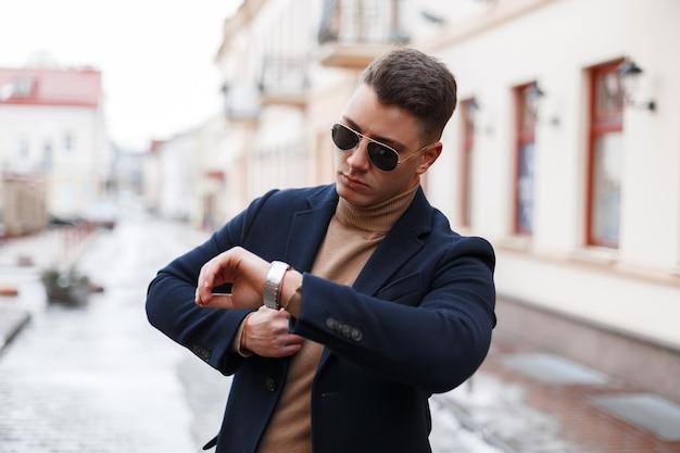 니트 스웨터에 세련된 헤어 스타일로 트렌디 한 선글라스에 우아한 코트에 세련된 젊은 사업가가 손에 보이는