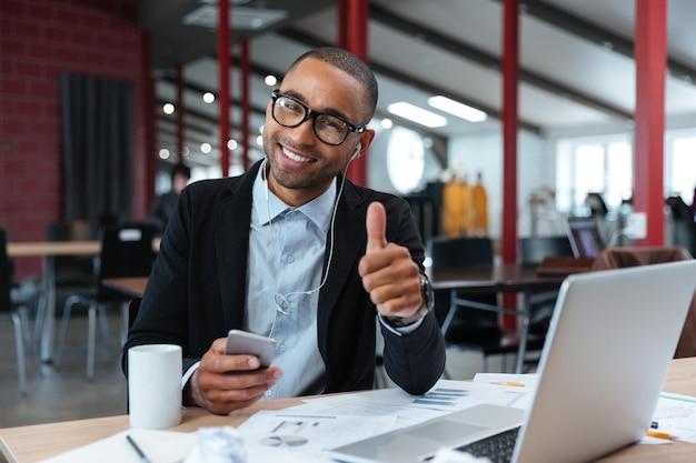 Стильный молодой бизнесмен показывает нормально знак и держит смартфон за ноутбуком
