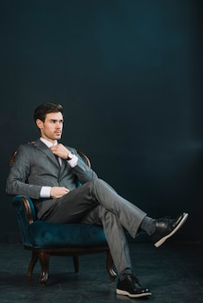 Stylish young businessman sitting on armchair against dark background
