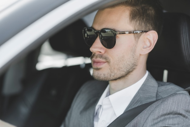 Stylish young businessman wearing sunglasses driving car