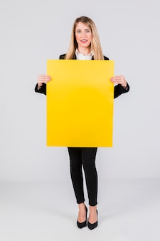 Stylish young businesswoman holding blank yellow placard standing against grey background