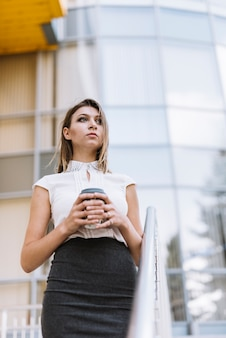 Stylish young businesswoman holding disposable coffee cup standing in front of corporate building