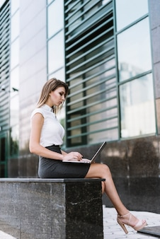 Stylish young businesswoman sitting on bench using laptop at outdoors