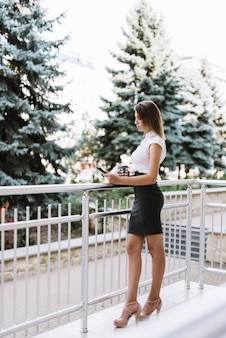 Stylish young businesswoman standing in the balcony looking at cellphone