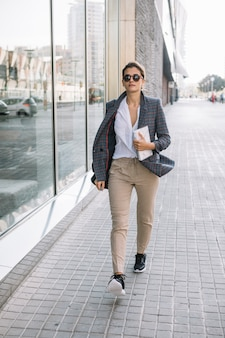 Stylish young businesswoman walking on sidewalk