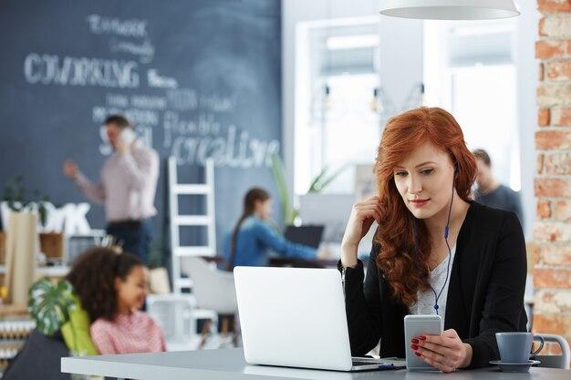 Стильная молодая деловая женщина, работающая на своем ноутбуке в современном офисе