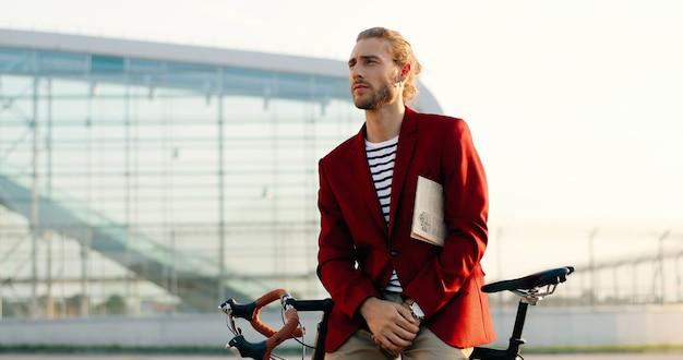 自転車に座って、屋外で新聞を読んで赤いジャケットを着たスタイリッシュな若い白人男性。自転車に寄りかかって紙を読むカジュアルなスタイルの男性。エアロポートストリートで。都市景観。