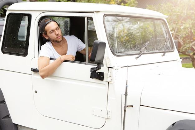 彼の白いスポーツユーティリティ車の開いているウィンドウを探しているスタイリッシュな若い白人男。野球帽をかぶったひげを剃っていない男性がジープを後方に運転し、ロードトリップを楽しんでいます