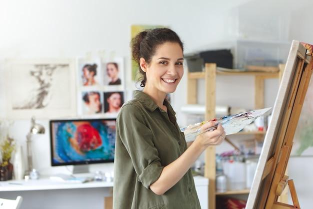 Стильная молодая кавказская женщина с темными волосами принимает участие в уроке и мастер-классе для художников, чувствуя себя счастливым и взволнованным, стоя в студии перед мольбертом и улыбается. искусство, обучение и образование