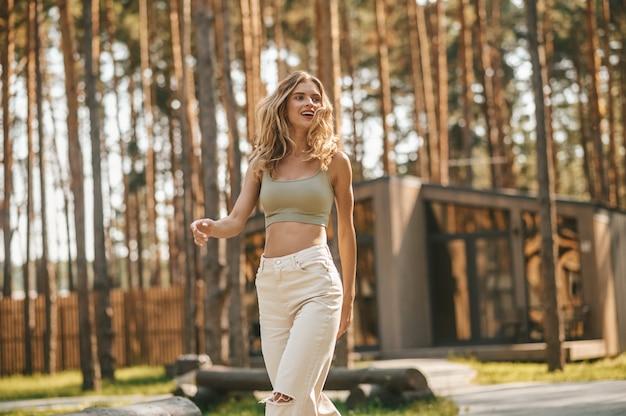 Стильная молодая веселая женщина гуляет в парке