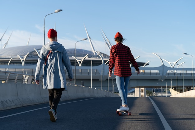 Stylish young couple in casual clothes longboard together boyfriend teach girlfriend to ride skate