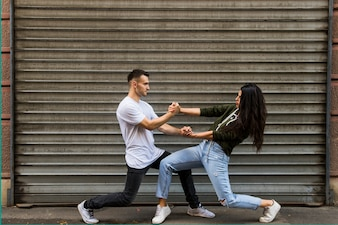 Stylish young couple dancing in front of corrugated wall
